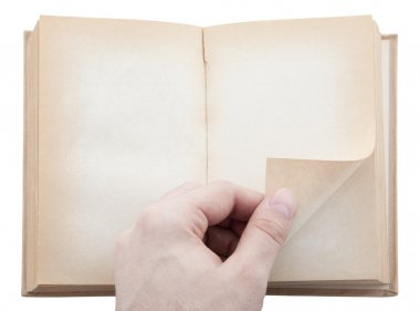 Hand turning old blank book page. Clipping path included.