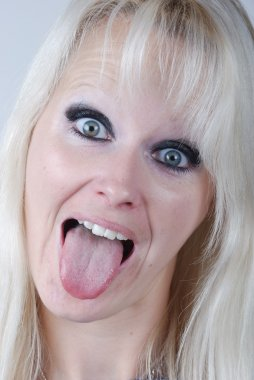 Young blonde woman sticking out her tongue