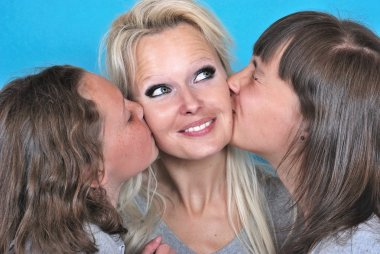 A mother smiles as she receives a kiss on the cheek from her you
