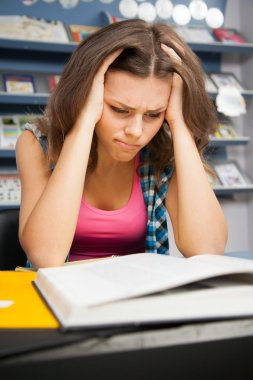 Stressed female student in a library