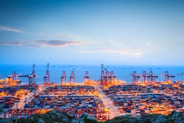 Shanghai container terminal in twilight ablaze with light stock vector