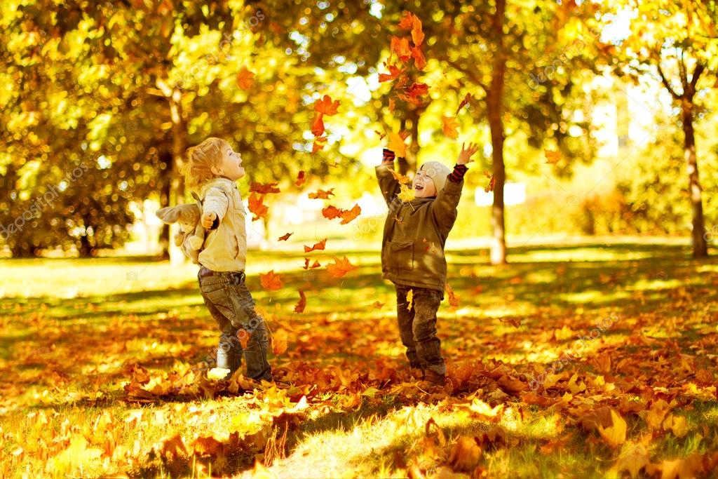 Children playing with autumn fallen leaves in park