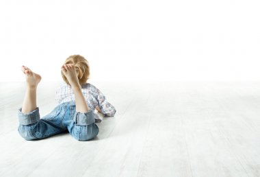 Child back lying down on floor and looking forward