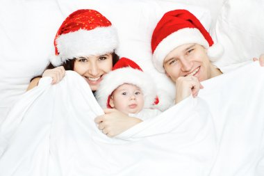 Christmas family in red hats lying in white bed