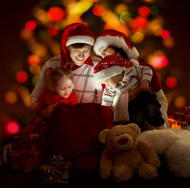 Happy family of four persons in red hats opening lighting bag