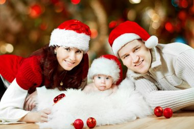 Christmas family of three persons in red hats
