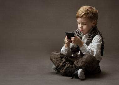 Boy playing game on cell phone. Kid sitting on grey background a