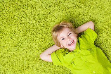 Child lying on the green carpet background.