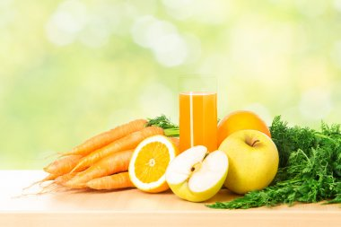 Fruit and vegetable juice in glass over green fresh background.