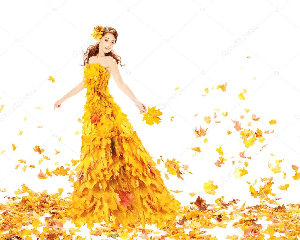 Autumn woman in fashion dress of maple leaves holding leaf