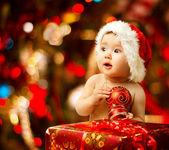 Weihnachtsbaby in Weihnachtsmütze in der Nähe von rotem Geschenkkarton