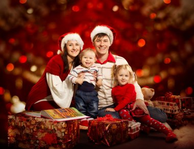 Christmas family of four persons happy smiling over red backgroud