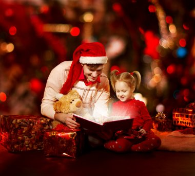 Christmas family reading book. Father and child opening magic fairy tal