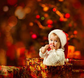 Christmas baby in Santa hat holding red ball near present gift box