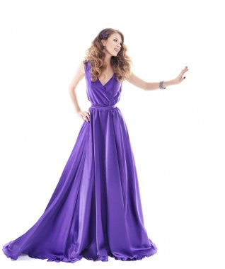 Woman showing advertisement in long purple silk dress over white background