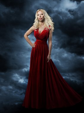 Woman in red dress over sky