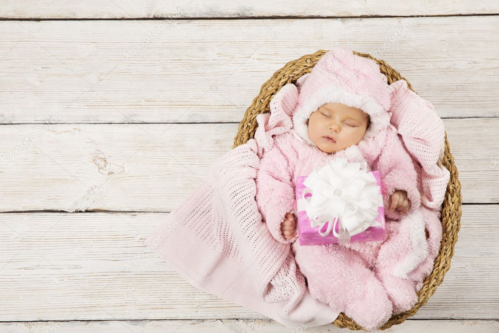 Baby girl with gift sleeping on wooden background newborn in basket baby girl with gift sleeping on wooden background newborn in basket with present birthday party invitation card photo by inarik stopboris Gallery