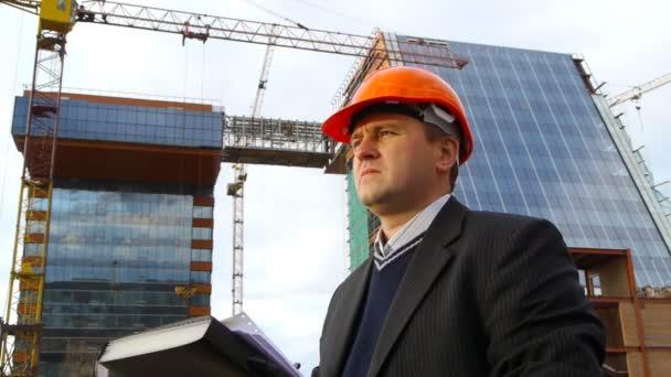 stavební inspektor s schránky na staveništi.