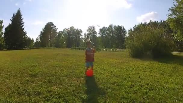 kisfiú játszik a labdát sz