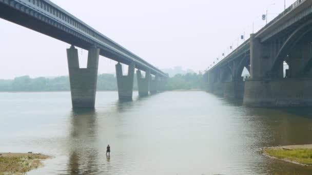 Muž, rybaření v řece pod mostem