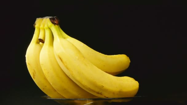 Bunch of bananas rotating on black background