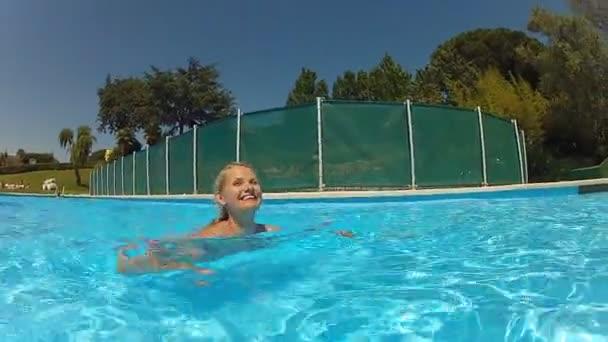 donna felice, nuotare in una piscina su vacanze estive