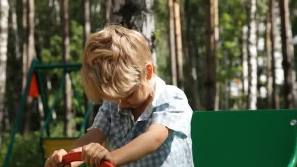 Happy boy playing in toy car on children playground.