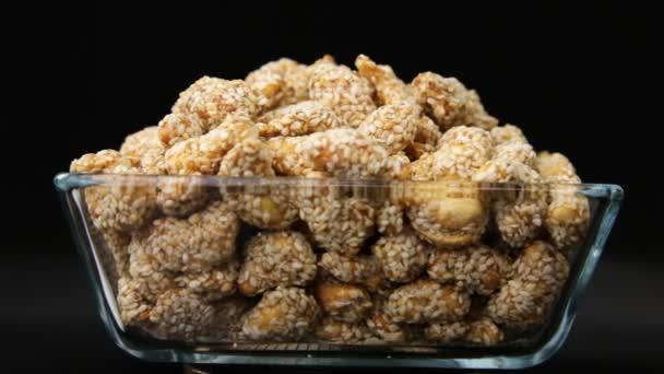 chutné oříšky sezamu a karamelem, izolované na černém