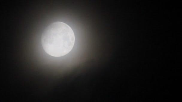 měsíc přes mlžné mraky na obloze