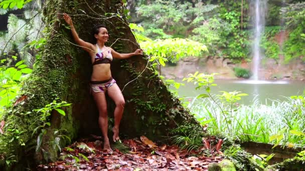 Sexy girl leaning huge tree in rainforest background waterfall