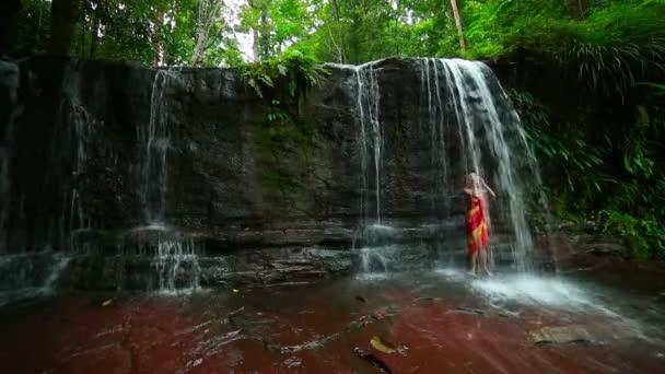Sexy girl with bikini taking a shower in waterfall