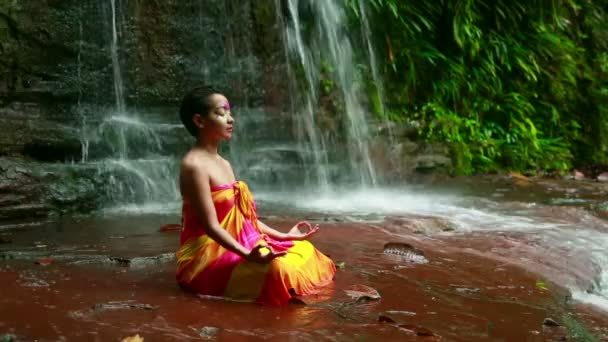 Meditating with Facial Painting in borneo rainforest waterfall