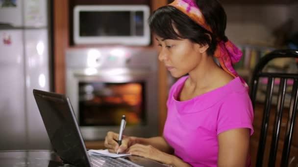 žena s laptopem psaní recept z Internetu v kuchyni