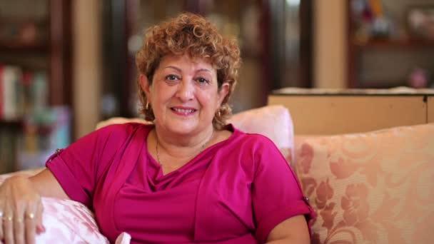 Seniorin sitzt im Wohnzimmer