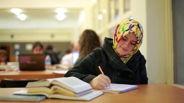 šťastná mladá studentka čtení knih v knihovně