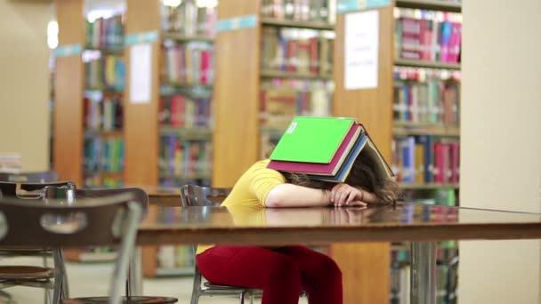 dívka spí pohřben pod kniha zásobníku v čítárně knihovny