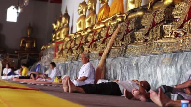 sedí pod zlatými sochami Buddhy