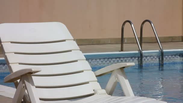Empty sunbed at swimming pool