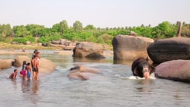Menschen und Elefanten am Fluss