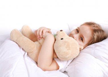 Cute girl cuddling with teddy bear