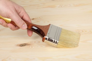 Hand with paintbrush on wood
