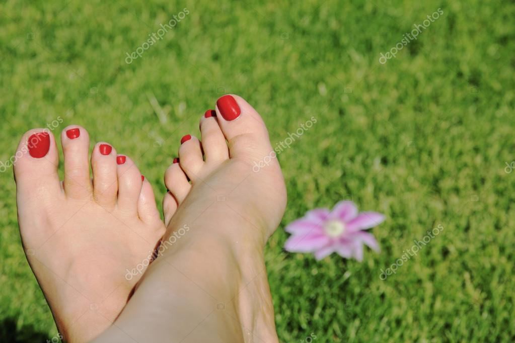 mujer de pie con uñas rojas sobre fondo de hierba con flores — Foto ...