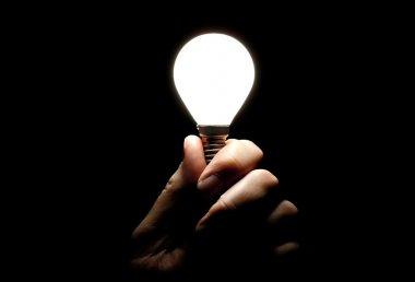 Light bulb held in hand on black background stock vector