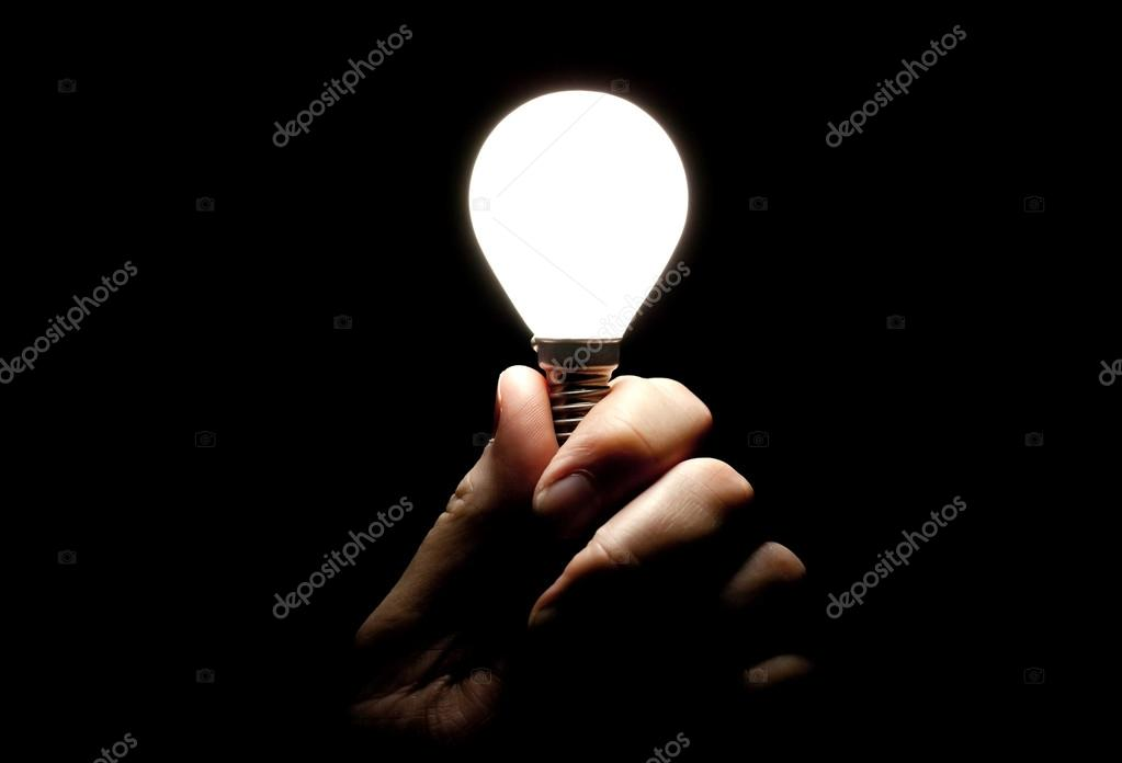 Lightbulb held in hand on black background