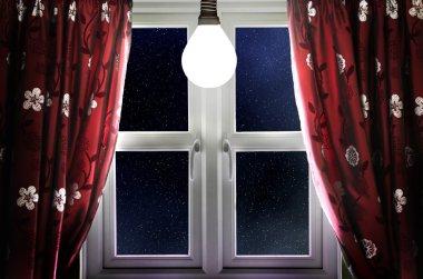 Light bulb shining in window