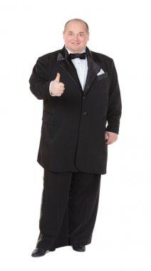 Elegant fat man in a tuxedo shows thumb-up