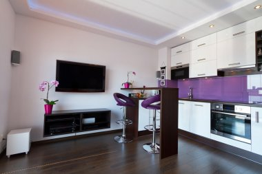 Modern living room with purple kitchen
