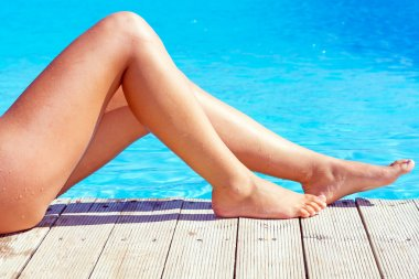 Sexy female legs at blue swimming pool