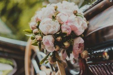 Bride's bouquet resting on a vintage wedding car