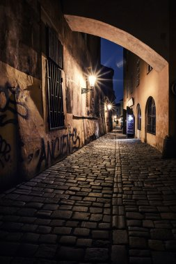 Narrow alley with lanterns in Prague at night